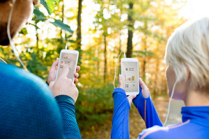 Unrecognizable couple running together outside in colorful sunny autumn forest using a fitness app on their smartphones. Using phone app for tracking weight loss progress, running goal or summary of their run. Rear view.