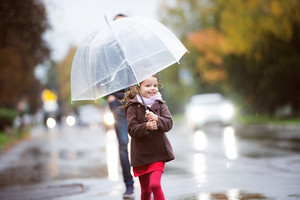 Unrecognizable father with cute little daughter under the umbrella. Walking in the street on a rainy day.