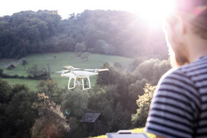 Unrecognizable hipster man with flying drone with camera. Green sunny nature. Rear view.