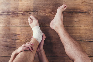 Unrecognizable injured runner sitting on a wooden floor background