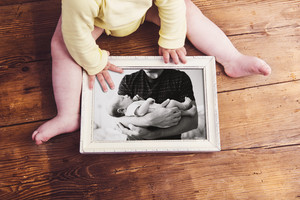 Unrecognizable little baby holding picture frame with picture of father and son. Studio shot on wooden background. Fathers day concept.