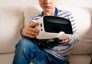 Unrecognizable little boy in striped t-shirt with virtual reality goggles. Sitting on white couch, studio shot