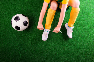 Unrecognizable little football player with soccer ball tying shoelaces, against artificial grass. Studio shot on green grass. Copy space.