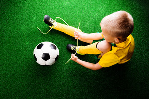 Unrecognizable little football player with soccer ball tying shoelaces, against artificial grass. Studio shot on green grass. Copy space