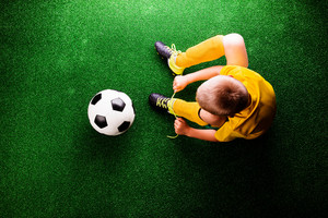 Unrecognizable little football player with soccer ball tying shoelaces, against artificial grass. Studio shot on green grass.