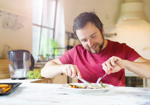 Unrecognizable man holding fork and knife cutting food on a plate