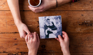Unrecognizable man holding womans hand. Looking  at their photo. Couple in love. Valentines day composition. Studio shot on brown wooden background.