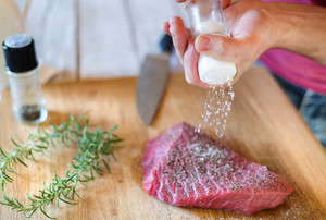 Unrecognizable man in the kitchen preparing beef steak