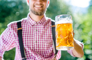 Unrecognizable man in traditional bavarian clothes holding mug of beer. Oktoberfest.