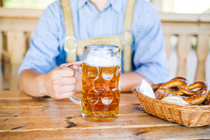 Unrecognizable man in traditional bavarian clothes sitting at the table with mug of beer. Pretzels in wicker basket. Oktoberfest.