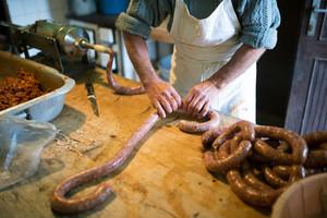 Unrecognizable man making sausages the traditional way using sausage filler. Homemade sausage.