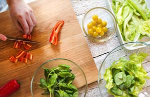 Unrecognizable man preparing ingredients for vegetable salad