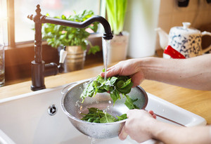 Unrecognizable man washing green salad leaves in the kitchen sink