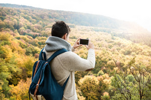 Unrecognizable man with backpack taking picture with his smart phone of colorful sunny autumn forest, rear view