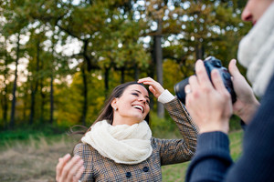 Unrecognizable man with camera taking pictures of his beautiful woman. Sunny autumn nature.