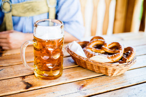 Unrecognizable men in traditional bavarian clothes sitting at the table with mug of beer. Pretzels in wicker basket. Oktoberfest.