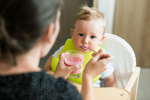 Unrecognizable mother feeding her baby daughter with fruit yogurt