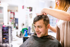 Unrecognizable professional hairdresser making new haircut to her handsome client. Barber at work. Man at barbershop.