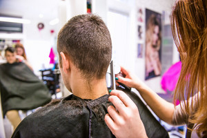 Unrecognizable professional hairdresser shaving head of her young client, making a new haircut. Barber at work. Man at barbershop.
