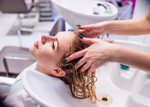Unrecognizable professional hairdresser washing hair to her beautiful client.  Young woman in a hair salon