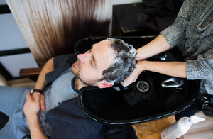 Unrecognizable professional hairdresser washing hair to her handsome client. Barber at work. Man at barbershop.