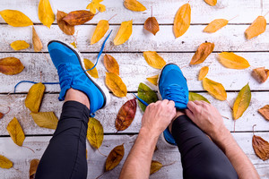 Unrecognizable runner in blue sports shoes tying shoelaces. Colorful autumn leaves. Studio shot on white wooden background.