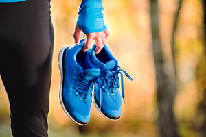 Unrecognizable runner in blue sweatshirt holding pair of sports shoes outside in colorful sunny autumn nature.