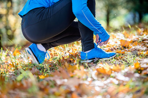 Unrecognizable runner in blue sweatshirt outside in colorful sunny autumn nature sitting on the ground, tying shoelaces