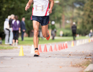 Unrecognizable runner sprinting outdoors. Sportive man competing in a urban area, healthy lifestyle and sport concepts.