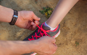 Unrecognizable runner tying shoelaces to his partner