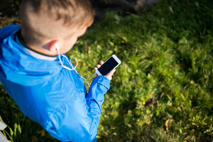 Unrecognizable runner with smart phone and earphones, listening music or using a fitness app. Using phone app for tracking weight loss progress, running goal or summary of his run. Outside in sunny autumn nature.