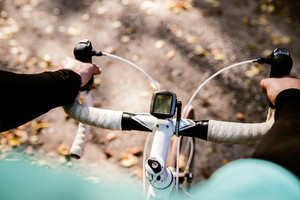 Unrecognizable sportsman riding his bicycle outside in sunny autumn nature, setting speedometer