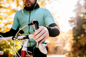 Unrecognizable sportsman riding his bicycle outside in sunny autumn nature