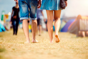 Unrecognizable teenage couple at tent music festival walking, sunny summer, close up of legs, back view, rear viewpoint