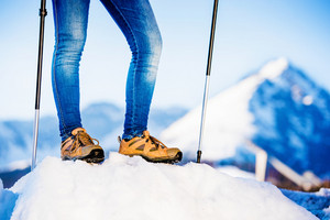 Unrecognizable woman hiking outside in sunny winter mountains