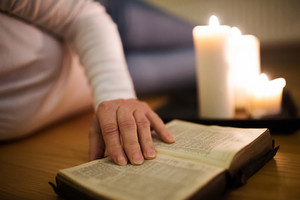 Unrecognizable woman lying on the floor reading her Bible. Burning candles next to her. Close up of the book and her hand.