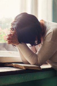 Unrecognizable woman reading her Bible and praying