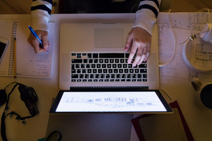 Unrecognizable woman sitting at desk at night working on laptop late at night, writing into notebook. Close up.
