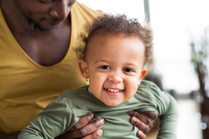 Unrecognizable young afro-american father at home with his cute little daughter holding her in the arms.
