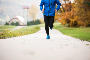Unrecognizable young athlete in blue jacket running outside in colorful sunny autumn nature on an asphalt path leading through green grass. Trail runner training for cross country running.