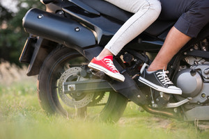 Unrecognizable young couple in love enjoying a motorbike ride in countryside. Close up of legs.
