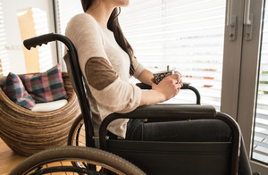 Unrecognizable young disabled woman in wheelchair at home in her living room, looking out the window, holding a cup of tea or coffee