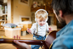 Unrecognizable young father at home playing guitar, his little son with earphones, listening music and dancing.