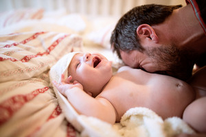 Unrecognizable young father tickling and snuggling his baby son with his beard. Boy lying on bed, wrapped in towel, drying after bath.