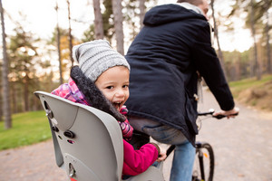 Unrecognizable young father with his daughter in bicycle seat in warm clothes cycling outside in autumn nature