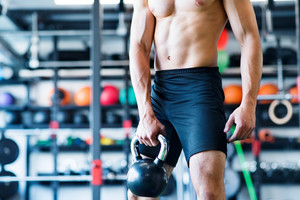 Unrecognizable young fit man doing strength training, exercising with kettlebell in modern gym.