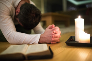 Unrecognizable young man praying, kneeling on the floor, hands clasped together. Bible and burning candles next to him. Close up.
