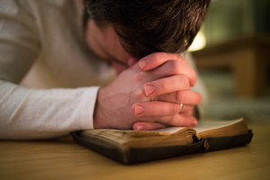 Unrecognizable young man praying, kneeling on the floor, hands on his Bible. Close up.