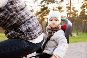 Unrecognizable young mother with her daughter in bicycle seat in warm clothes cycling outside in autumn nature