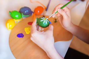 Unrecognizable young woman hand painting easter eggs